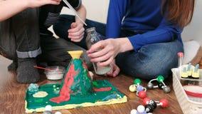 Χημικό πείραμα Η κινηματογράφηση σε πρώτο πλάνο του αγοριού ` s δίνει το χυμένο νερό από το μπουκάλι στη χοάνη του ηφαιστείου χρη απόθεμα βίντεο