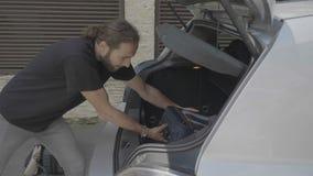 Χιλιετές ευτυχές άτομο που πηγαίνει στον κορμό ανοίγματος διακοπών και φόρτωση του αυτοκινήτου hatchback με τις βαλίτσες ταξιδιού απόθεμα βίντεο