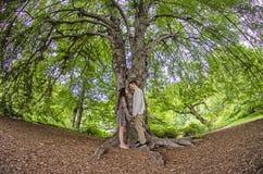 Χιλιετές ζεύγος πρόσωπο με πρόσωπο κάτω από ένα μεγάλο δέντρο στοκ φωτογραφίες