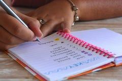 Χιλιετής γυναίκα, που γράφει σε ένα περιοδικό σφαιρών στοκ φωτογραφία