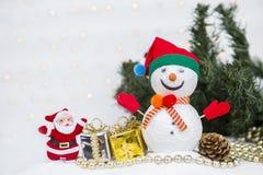 Χιονάνθρωπος και Άγιος Βασίλης με τη διακόσμηση χριστουγεννιάτικων δέντρων πέρα από το θολωμένο φως bokeh στοκ εικόνα με δικαίωμα ελεύθερης χρήσης