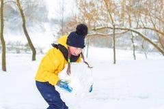 Χιονάνθρωπος μικρών κοριτσιών sculpts το παιδί φέρνει ένα κομμάτι του χιονιού στοκ φωτογραφία με δικαίωμα ελεύθερης χρήσης