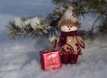 Χιονάνθρωπος παιχνιδιών με ένα δώρο στο χιόνι Στοκ φωτογραφία με δικαίωμα ελεύθερης χρήσης