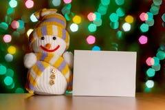 Χιονάνθρωπος παιχνιδιών που κρατά ένα σημάδι για το κείμενό σας στο υπόβαθρο των φω'των γιρλαντών Στοκ Εικόνες