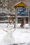 Χιονάνθρωπος στο πάρκο Φωτογραφική διαφάνεια και ξύλινο σπίτι Στοκ Φωτογραφία