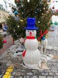 Χιονάνθρωπος στο υπόβαθρο ενός χριστουγεννιάτικου δέντρου στοκ φωτογραφία