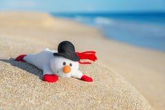 Χιονάνθρωπος Χριστουγέννων παιχνιδιών Smiley στην καυτή παραλία θάλασσας Στοκ Εικόνες