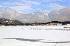 Χιονισμένα λίμνη, βουνά, δάση και σύννεφα σωρειτών Στοκ Φωτογραφία