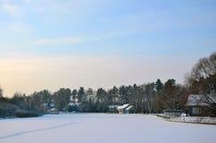 Χιονισμένα λίμνη και σπίτια στο χειμερινό δασικό υπόβαθρο Ημέρα των Χριστουγέννων στοκ φωτογραφία με δικαίωμα ελεύθερης χρήσης
