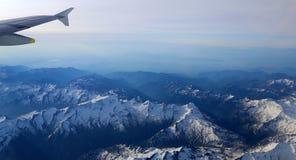 Χιονισμένες αιχμές βουνών με τα αεροσκάφη ύψους Στοκ εικόνες με δικαίωμα ελεύθερης χρήσης