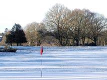 Χιονισμένο γήπεδο του γκολφ με τη κόκκινη σημαία, Chorleywood κοινό στοκ φωτογραφίες