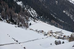 Χιονισμένο ορεινό χωριό στο πόδι του βουνού το χειμερινό απόγευμα στοκ εικόνες