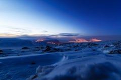 Χιονισμένο mountainside, φωτογραφία νύχτας Στην απόσταση οι μύλοι χάλυβα στοκ φωτογραφίες με δικαίωμα ελεύθερης χρήσης