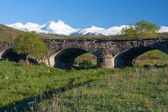 Χιονοσκεπές βουνό Aragats και αρχαία γέφυρα σε πράσινο Στοκ φωτογραφία με δικαίωμα ελεύθερης χρήσης