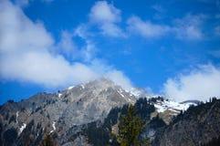 Χιονοσκεπή βουνά ενάντια στον ουρανό Στοκ Εικόνα