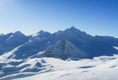 Χιονώδεις αιχμές των καυκάσιων βουνών στο μπλε ουρανό Περιοχή Elbrus στοκ εικόνα