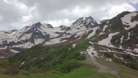Χιονώδεις κορυφές βουνών και δύο μικρών σπιτιών στον εναέριο πυροβολισμό κοιλάδων στοκ εικόνες