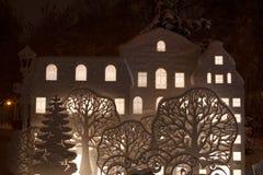 Χιονώδεις κτήρια και σκιαγραφίες δέντρων στη χειμερινή νύχτα στοκ εικόνες