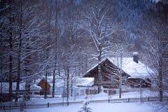 Χιονώδες αλπικό σπίτι στα δάση Στοκ εικόνα με δικαίωμα ελεύθερης χρήσης