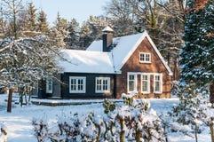 Χιονώδες ξύλινο σπίτι στο δάσος Στοκ Φωτογραφία