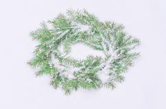 Χιονώδες παγωμένο στεφάνι Χριστουγέννων Στεφάνι των κλάδων έλατου στο χιόνι Στοκ εικόνα με δικαίωμα ελεύθερης χρήσης