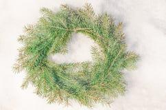 Χιονώδες παγωμένο στεφάνι Χριστουγέννων Στεφάνι των κλάδων έλατου στο χιόνι Στοκ φωτογραφίες με δικαίωμα ελεύθερης χρήσης