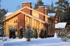 Χιονώδες υπόβαθρο εξοχικών σπιτιών ενός πρωινού χειμερινών δασικού Χριστουγέννων στοκ φωτογραφία