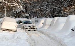Χιονώδης δρόμος και καλυμμένα αυτοκίνητα Στοκ Φωτογραφίες
