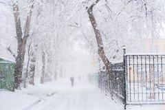 Χιονώδης δρόμος πόλεων μεταξύ των δέντρων και των μόλις ορατών περπατώντας ανθρώπων κατά τη διάρκεια των άφθονων χιονοπτώσεων στοκ φωτογραφία με δικαίωμα ελεύθερης χρήσης