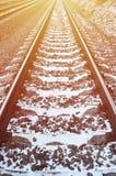 Χιονώδης ρωσικός χειμερινός σιδηρόδρομος λεπτομερειών κάτω από το φωτεινό φως του ήλιου Οι ράγες και οι κοιμώμεοί κάτω από το χιό Στοκ εικόνα με δικαίωμα ελεύθερης χρήσης