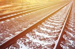 Χιονώδης ρωσικός χειμερινός σιδηρόδρομος λεπτομερειών κάτω από το φωτεινό φως του ήλιου Οι ράγες και οι κοιμώμεοί κάτω από το χιό Στοκ εικόνες με δικαίωμα ελεύθερης χρήσης