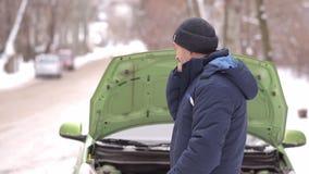 Χιονώδης χειμώνας Ένα άτομο καλεί ένα φορτηγό ρυμούλκησης στο υπόβαθρο ενός σπασμένου αυτοκινήτου με μια ανοικτή κουκούλα φιλμ μικρού μήκους