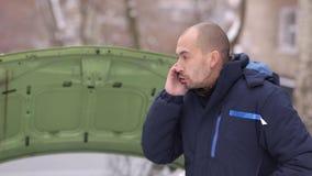 Χιονώδης χειμώνας Ένα άτομο καλεί ένα φορτηγό ρυμούλκησης στο υπόβαθρο ενός σπασμένου αυτοκινήτου με μια ανοικτή κουκούλα απόθεμα βίντεο