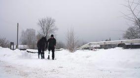 Χιονώδης χειμώνας, εκτός λειτουργίας jockey ατόμων οδηγεί, κρατώντας με τα ηνία ένα μαύρο άλογο στον τρόπο το άτομο έχει μια πρόσ απόθεμα βίντεο