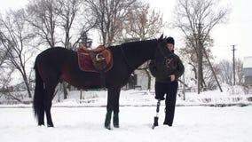 Χιονώδης χειμώνας, εκτός λειτουργίας jockey ατόμων στέκεται κοντά στο μαύρο άλογο υπαίθρια έχει την πρόσθεση αντί του σωστού ποδι απόθεμα βίντεο