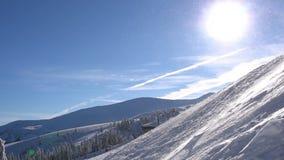 Χιονώδης χιονοθύελλα στα βουνά στον όμορφο ηλιόλουστο καιρό φιλμ μικρού μήκους