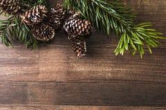 Χιονώδεις κώνοι και κλάδος έλατου σε ένα ξύλινο υπόβαθρο Στοκ Εικόνες
