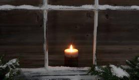 Χιονώδεις κλάδοι παραθύρων και έλατου με το καμμένος κερί Στοκ φωτογραφία με δικαίωμα ελεύθερης χρήσης