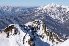 Χιονώδεις κλίσεις σκι και cableway καρεκλών ανελκυστήρες στο όμορφο τοπίο θερέτρου χειμερινών βουνών του Sochi Krasnaya Polyana Στοκ Εικόνες
