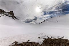Χιονώδεις πέρασμα και ουρανός βουνών με τα σύννεφα στο βράδυ Στοκ Εικόνες
