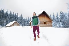 Χιονώδες εξοχικό σπίτι θερέτρου χειμερινού χιονιού του χωριού ξύλινο εξοχικών σπιτιών νεαρών άνδρων Στοκ Φωτογραφία