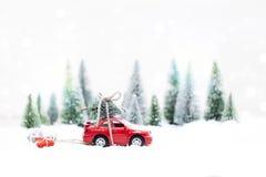 Χιονώδες χειμερινό δάσος με το μικροσκοπικό κόκκινο αυτοκίνητο που φέρνει Χριστούγεννα Στοκ Φωτογραφίες
