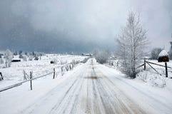 Χιονώδες χειμερινό τοπίο νεράιδων με έναν χιονισμένο αγροτικό δρόμο Στοκ Εικόνες