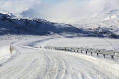 Χιονώδης και παγωμένος δρόμος με τα ηφαιστειακά βουνά στο wintertime Στοκ Εικόνες