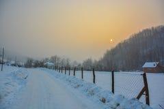 Χιονώδης πορεία εκτός από την ξύλινη καλύβα πριν από το ηλιοβασίλεμα Στοκ φωτογραφία με δικαίωμα ελεύθερης χρήσης