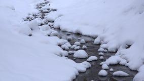 Χιονώδης ροή του νερού κολπίσκου στο κανάλι χειμερινών πάρκων Πτώση χιονιού Ζουμ μέσα 4K απόθεμα βίντεο