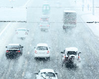 Χιονώδης χειμερινός δρόμος με την οδήγηση αυτοκινήτων στο οδόστρωμα στη θύελλα χιονιού Στοκ Εικόνα