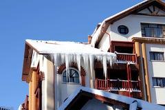 Χιονώδης χειμώνας σπιτιών με τα παγάκια Στοκ Φωτογραφία