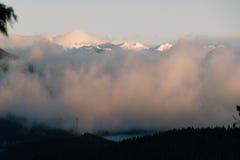 Χιονώδη ορατά ανωτέρω σύννεφα βουνών με τη λίμνη κάτω Στοκ εικόνα με δικαίωμα ελεύθερης χρήσης