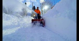 Χιόνι καθαρίσματος ατόμων με τον ανεμιστήρα 4k χιονιού απόθεμα βίντεο
